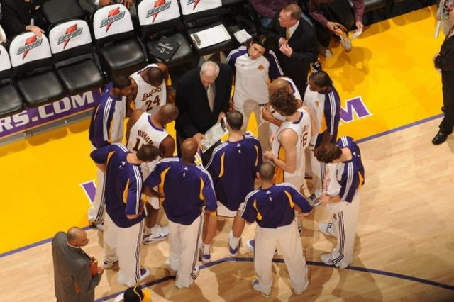 Lakers team gather around Phil Jackson during a timeout